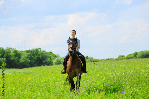 Obraz na plátně The Caucasian horsewoman is riding on the grass on the summer day