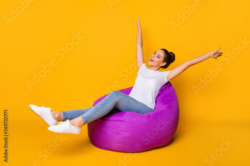 Portrait of her she nice-looking attractive lovely pretty slim fit thin cheerful cheery girl sitting in bag chair having fun isolated over bright vivid shine vibrant yellow color background