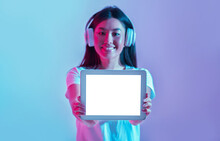 New Generation Of Devices. Smiling Asian Girl In Headphones Shows Tablet With Blank Screen On Pink And Blue Background In Light Of Neon