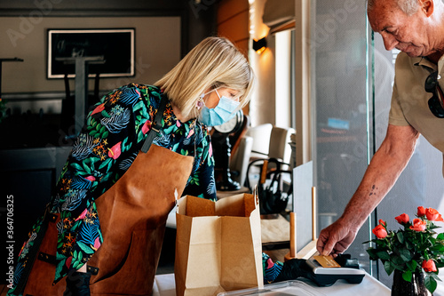 customer and bartender with a protective mask, making electronic payment on the Canvas