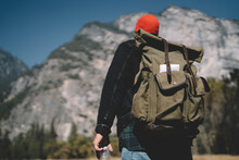 Back View Of Male Traveler Looking Up On High Mountain Exploring And Discovering National Park Landscape Of Active Leisure Trip, Hipster Guy Tourist With Rucksack Trekking Path In Forest Recreating