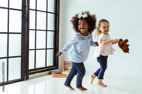 Fototapeta Candid portrait of two energetic playful young diverse friends children playing indoors