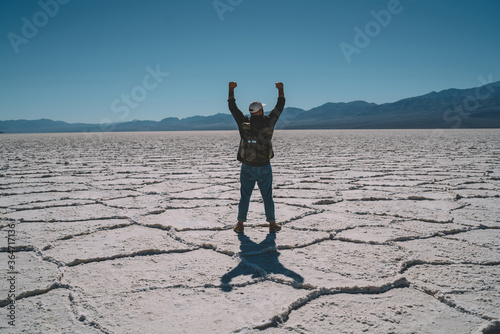 Leinwand Poster Back view of male wanderlust with touristic backpack raising arms completed marathon in Badwater basin, young hipster guy feeling success and freedom looking at breathtaking scenery of desert