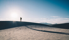 Silhouette Of Male Person Wanderlust Standing On Beautiful Dunes Peak Enjoying Freedom Of Travel Lifestyle Durin Sunset. Man Wanderlust Standing On Sand Hill At Sunrise In Scenery Nature Landscape