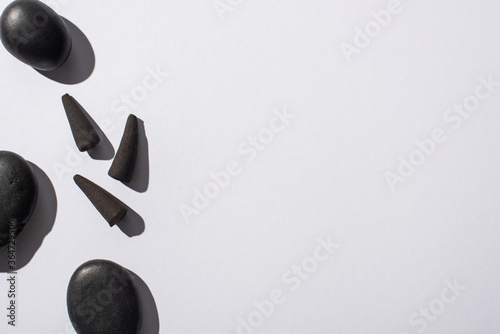 Fotografie, Obraz top view of black incense cones and spa stones on white background