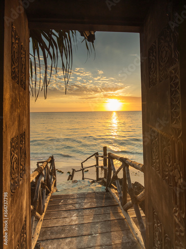 Fototapeta Beautiful dor way to white beach with sunrise in background. Zanzibar obraz