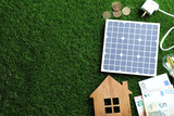 Fototapeta Kawa jest smaczna - Flat lay composition with solar panel, house model and money on green grass. Space for text