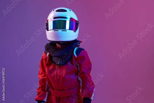Fotografia Cool boy child racer in helmet, racing suit, standing in neon light