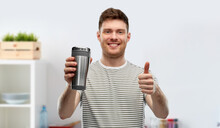 Eco Living And Sustainability Concept - Happy Smiling Young Man In Striped T-shirt With Thermo Cup Or Tumbler For Hot Drinks Over Home Kitchen Background