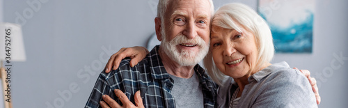 horizontal image of happy senior couple smiling and embracing while looking at c Canvas