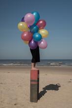 Girl Standing On Pole Onj Beac...