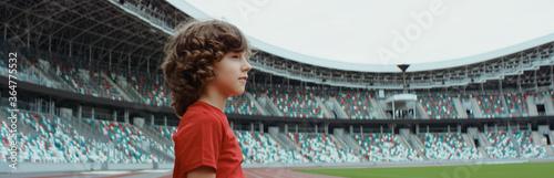 Valokuvatapetti Cute little kid boy soccer player standing on an empty stadium, dreaming of beco
