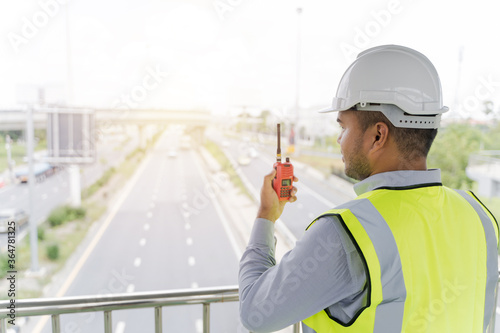 Portrait engineer handsome man or architect looking construction with the command of a radio Fotobehang