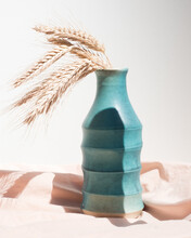 Still Life With Wheat Ears And A Turquoise Vase On Rose Draped Fabric And White Background