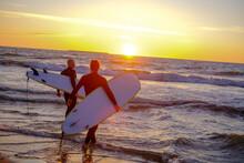 Unrecognizable Surfers Enterin...