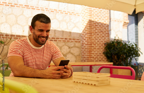 Man sitting on a terrace with his cell phone Fototapete