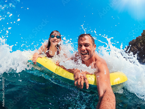 Father and daughter having fun on the beach while floating on airbed Wallpaper Mural