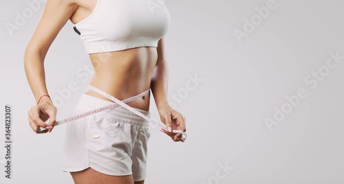 Fotomural Beautiful fitness girl measuring her waistline with measure tape