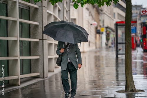 Middle-aged businessman wearing a suit caught out in the rain during a windy  dr Canvas Print