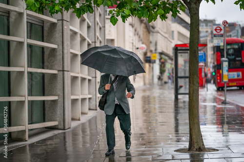 Middle-aged businessman wearing a suit caught out in the rain during a windy  dr Wallpaper Mural