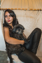Girl Petting Her Pet, A Black Shitzu Dog, Dressed In A Red Blouse And Black Pants, With A Red Bow On Her Head, Sitting On Her Lap Comfortably, An Afternoon Of Total Relaxation.