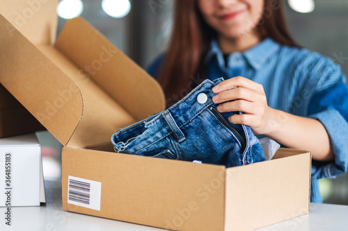 A beautiful young asian woman receiving and opening a postal parcel box of cloth Tapéta, Fotótapéta