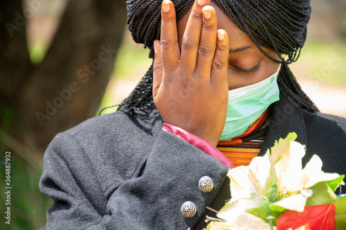 Photo young african woman mourning, wearing black and holding flowers