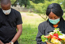 Black People Mourning Lost Ones To Coronavirus, Wearing Face Masks, Physical Distancing