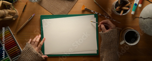 Photo Female artist drawing on sketch paper on wooden worktable with painting tools an