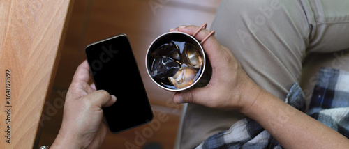 Male hand holding ice coffee mug and using smartphone while relaxed sitting at w Canvas Print