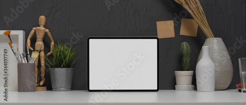 Photo Mock up tablet on trendy worktable with painting brushes and decorations