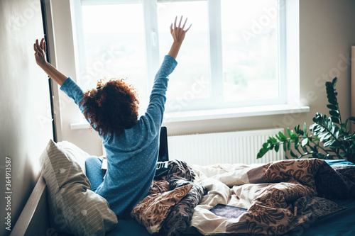 Obraz Curly haired caucasian woman in blue pajama stretching up in bed early morning - fototapety do salonu