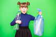 canvas print picture - Girl hold trash bag and plastic bottle and shows interest in environmental issues isolated on green background. Child accustomed to bear responsibility for garbage since childhood.