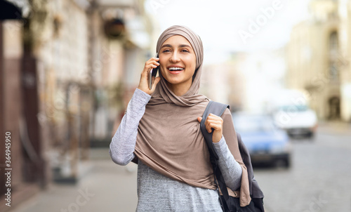 Girl in hijab talking on phone while walking by city Canvas Print