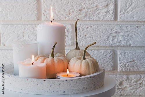 Leinwand Poster Autumn home decor with white pumpkins and burning candles.