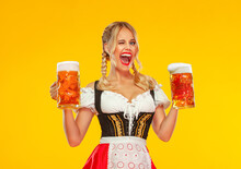 Young Sexy Oktoberfest Girl Waitress, Wearing A Traditional Bavarian Or German Dirndl, Serving Big Beer Mugs With Drink Isolated On Yellow Background. Woman Pointing To Looking Left.