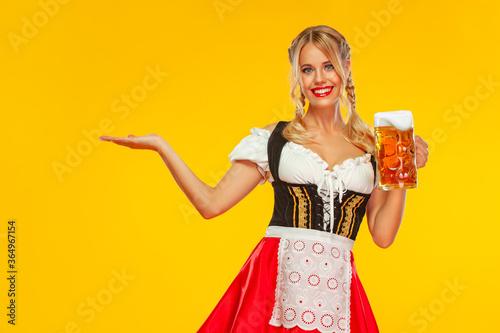 Billede på lærred Young sexy Oktoberfest girl waitress, wearing a traditional Bavarian or german dirndl, serving big beer mug with drink isolated on yellow background