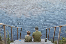 Happy Grandfather And Grandson Fishing Together, Sitting On Wooden Placing Near River, Holding Fishing Rod In Hands, Enjoying Beautiful Nature And Silence.