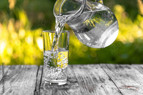 Carta da parati A glass glass is filled with clear water from a jug on a background of greenery