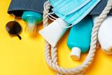Fototapeta Kawa jest smaczna - Blue beach bag with beach accessories and protective mask on yellow background