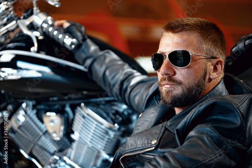 Photo Cool man biker in sunglasses sitting near his motocycle