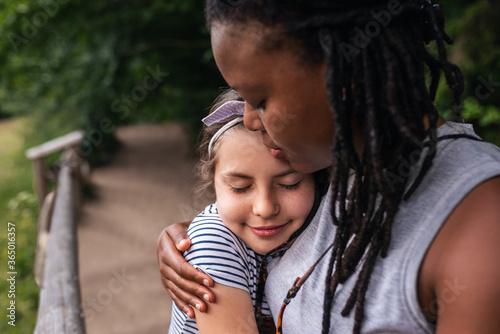 Fototapeta Smiling woman hugging a little girl during a hiking break