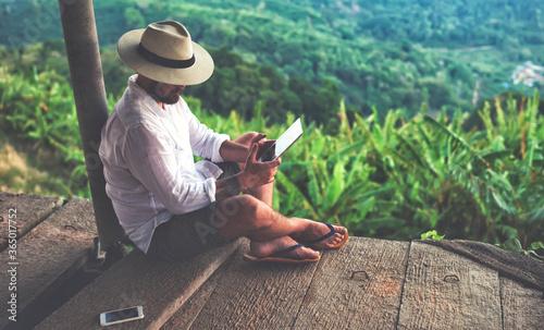 Man traveler is using digital tablet, while is sitting against beautiful Asian scenery during summer journey Fototapeta
