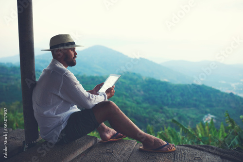Slika na platnu Man wanderer enjoying amazing jungle landscape and holding in hands portable touch pad with copy space on the screen