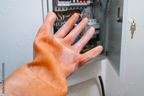 Obraz Demonstration of a dielectric glove for working with electricity - fototapety do salonu