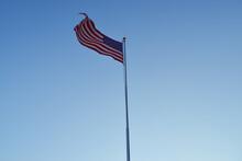 American Flag Waving In Wind Against Clear Blue Sky