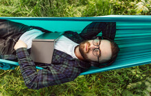 Bearded Hipster Male Reading Book In Hammock