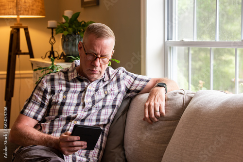 Canvas-taulu Mature man reading kindle on living room couch