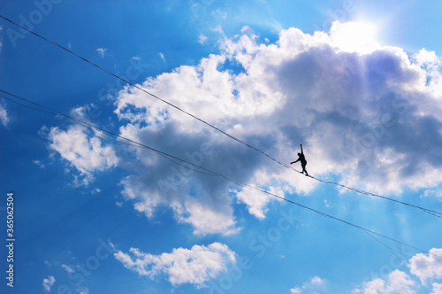 Valokuvatapetti A silhouette of a man balancing on a rope against a background of blue sky and clouds
