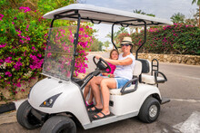 Mom And Daughter Sit In A Golf Cart. Family Rides An Electric Car In A Beautiful Resort. Tourists Relax On Vacation.